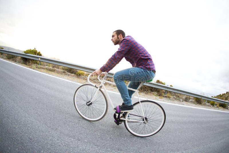 Vélo fixe de monte de sport de vitesse d'homme de cycliste dans le jour ensoleillé image stock