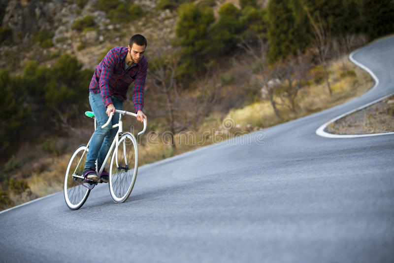 Vélo fixe de monte de sport de vitesse d'homme de cycliste dans le jour ensoleillé photographie stock libre de droits