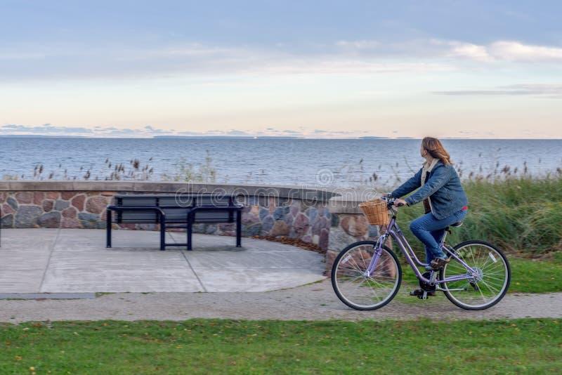 Vélo gai d'équitation de femme le long de rivage du lac Supérieur dans la chute photos stock