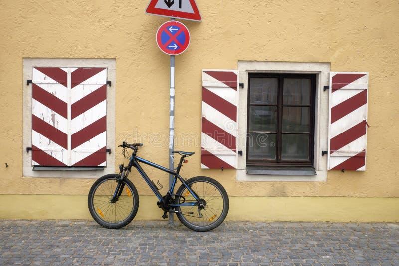 Vélo garé au mur de la maison et d'un arrêt d''No de panneau routier photographie stock
