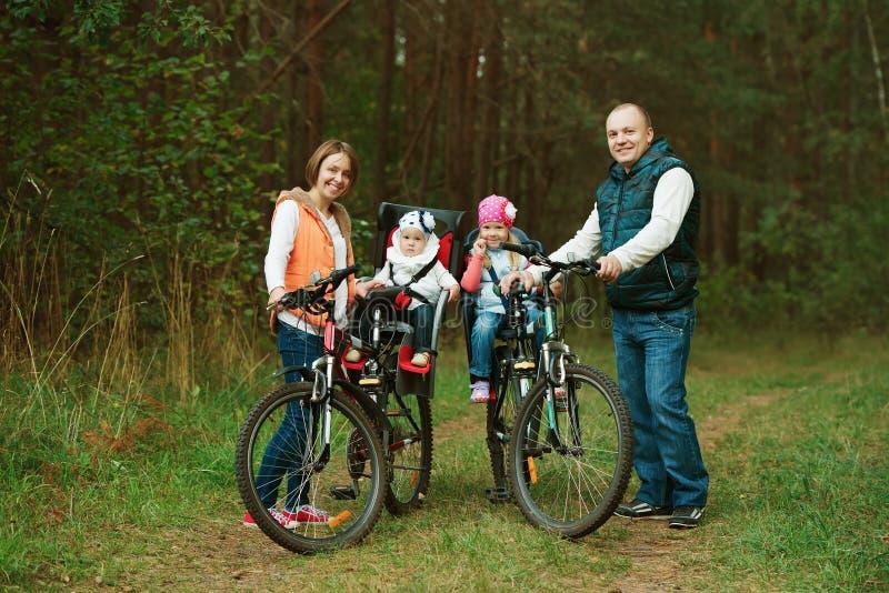 Vélo heureux d'équitation de famille en bois photos stock