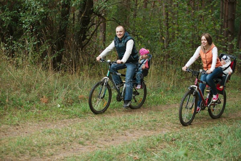 Vélo heureux d'équitation de famille en bois image stock