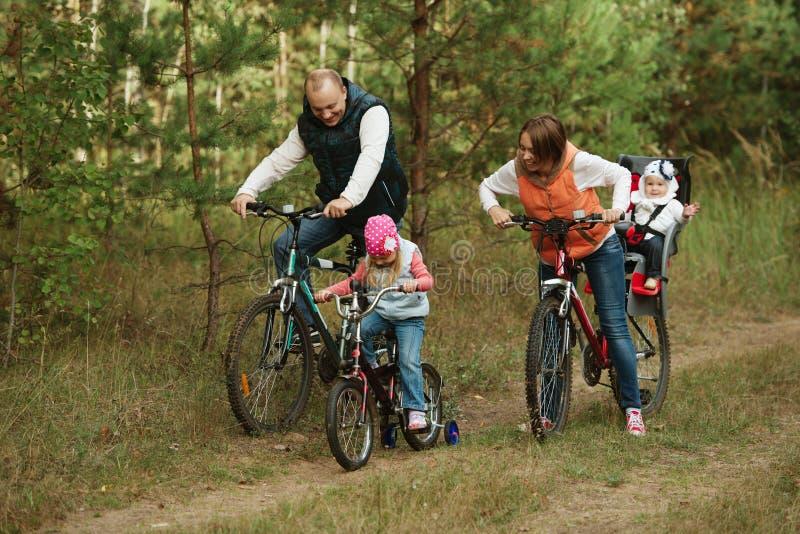 Vélo heureux d'équitation de famille en bois photo stock