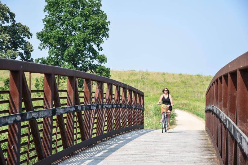 Vélo heureux d'équitation de femme au-dessus de pont image stock