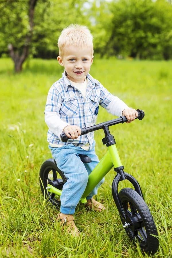 Vélo heureux d'étudiant d'équitation de petit garçon photo stock