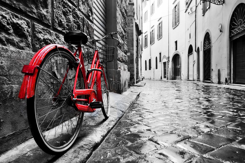 Vélo rouge de rétro vintage sur la rue de pavé rond dans la vieille ville Couleur en noir et blanc photo stock