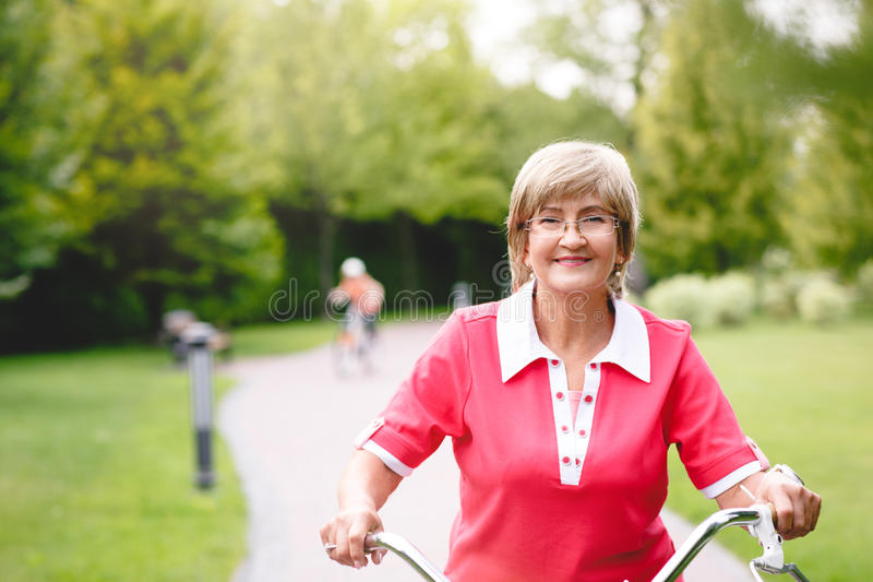 Vélo supérieur actif d'équitation de femme en parc photographie stock