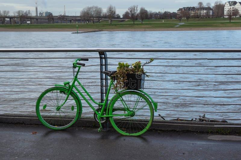 Vélo vert sur le remblai de la rivière sous la pluie dans la perspective des maisons image stock