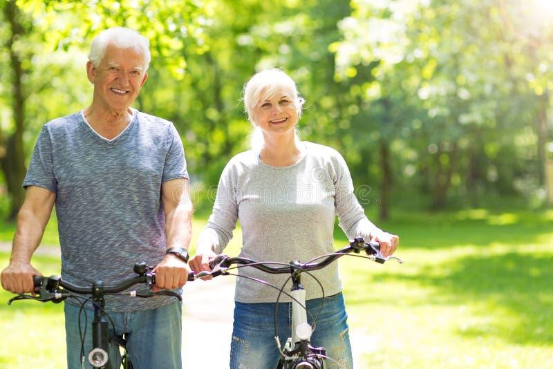 Vélos aînés d'équitation de couples photos libres de droits