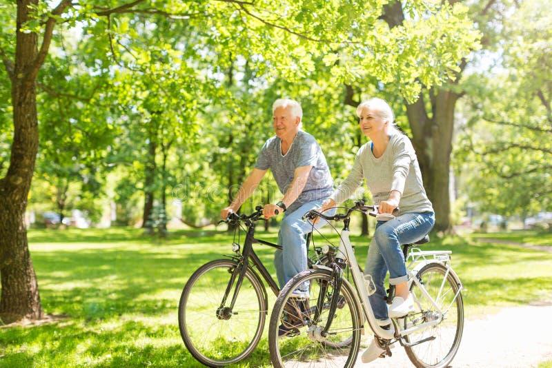 Vélos aînés d'équitation de couples photographie stock