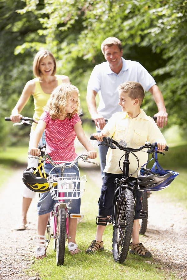 Vélos d'équitation de famille dans la campagne photographie stock libre de droits