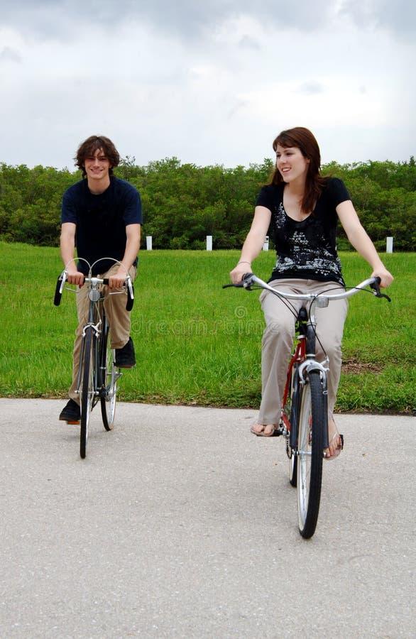 Vélos de l'adolescence d'équitation de couples photographie stock