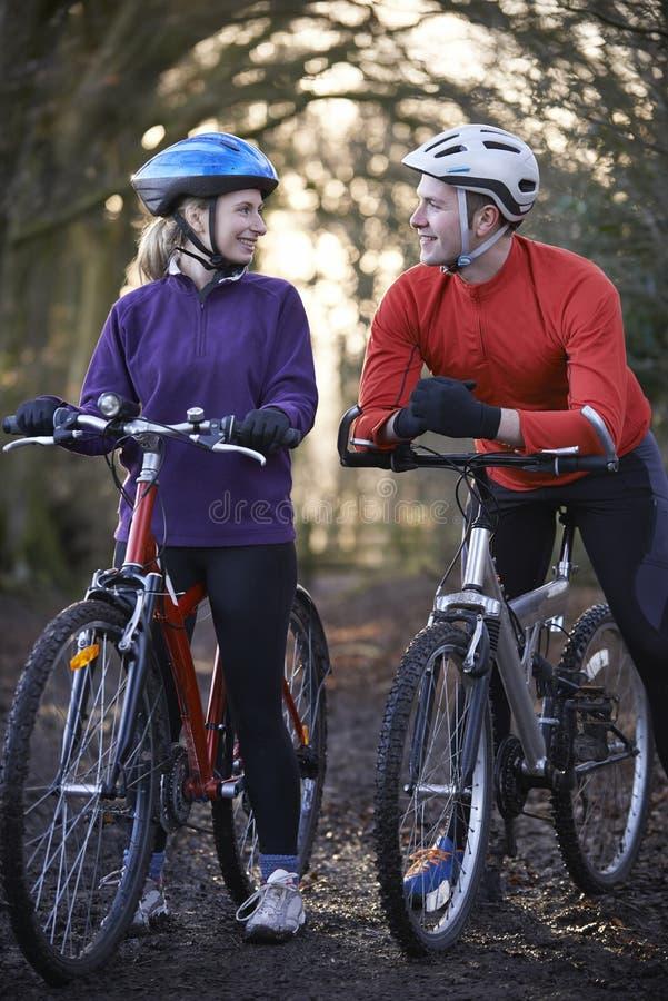 Vélos de montagne d'équitation de couples par des régions boisées photo stock