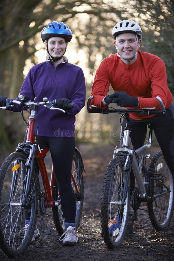 Vélos de montagne d'équitation de couples par des régions boisées images stock