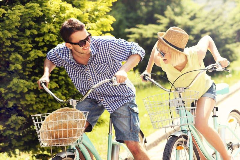 Vélos heureux d'équitation de couples photos libres de droits