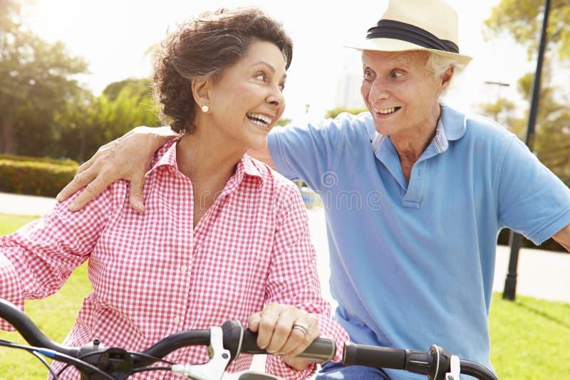 Vélos hispaniques aînés d'équitation de couples en stationnement image stock