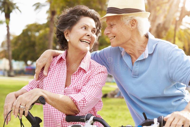 Vélos hispaniques aînés d'équitation de couples en stationnement photos stock
