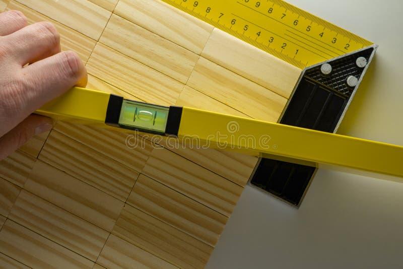 Vérification du niveau de la table, main avec le niveau de bâtiment ou waterpas et table en bois de blocs image libre de droits