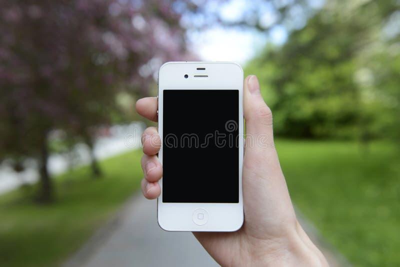 Vérifiez le téléphone pendant la marche sur la rue photographie stock