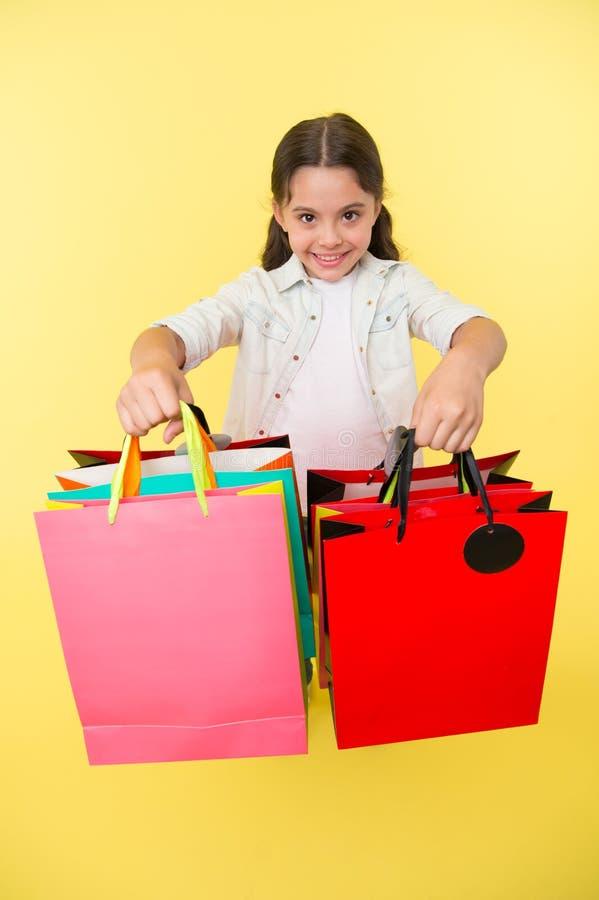 Vérifiez ses paquets d'achats La fille porte le fond jaune de paniers Fille affectueuse des achats Enfant mignon images libres de droits