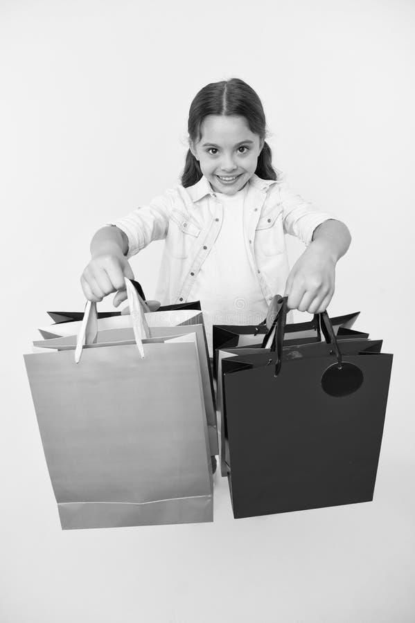 Vérifiez ses paquets d'achats La fille porte le fond jaune de paniers Fille affectueuse des achats Enfant mignon photo stock