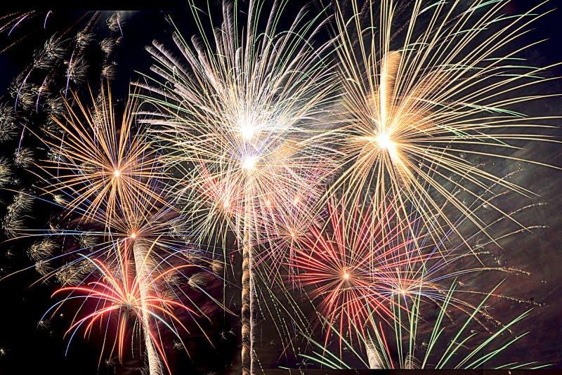 A véspera do ` s do ano novo e o quarto de fogos-de-artifício de julho em Florida sul cobrem o céu noturno com as explosões de co fotografia de stock