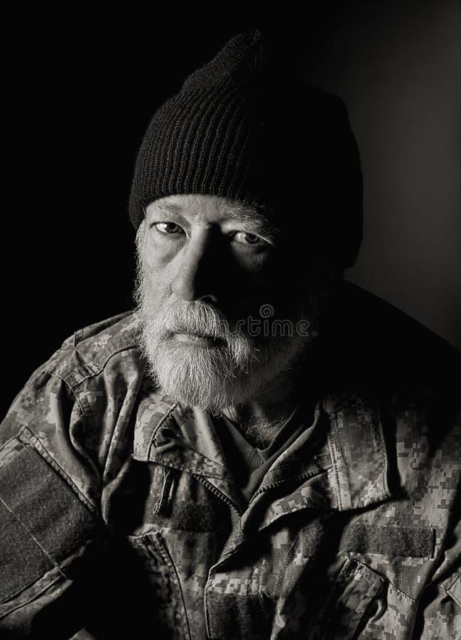 Vétéran sérieux utilisant une veste de camo et un chapeau de knit photographie stock