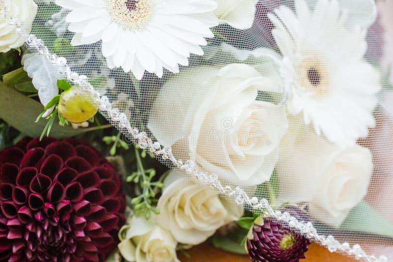 Véu do casamento sobre o ramalhete nupcial da dália, das rosas, e dos gerberas brancos foto de stock royalty free