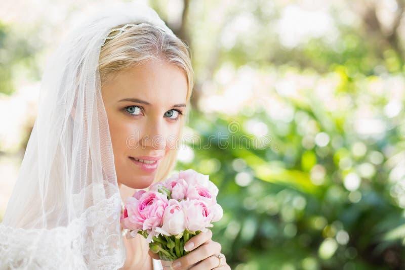 Véu vestindo de sorriso da noiva que guarda o ramalhete que olha a câmera imagem de stock