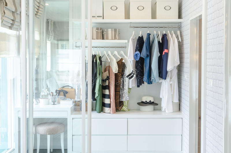 Vêtements accrochant dans le cabinet avec le chapeau photographie stock