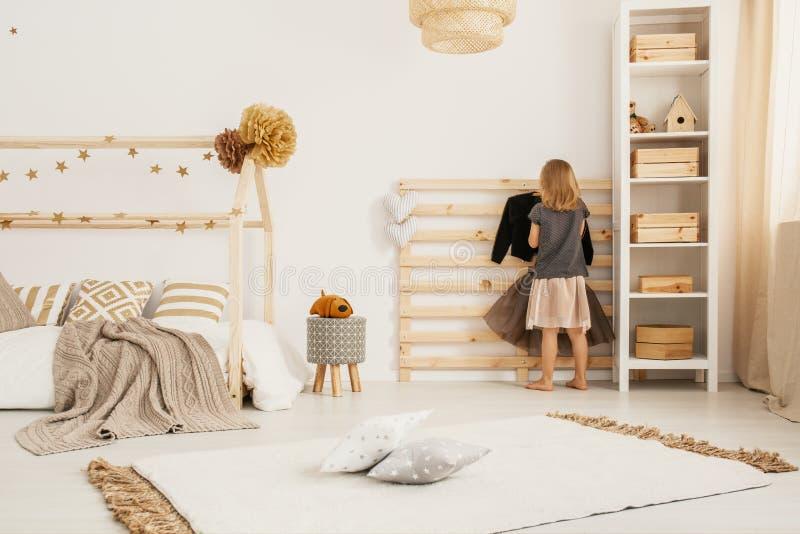 Vêtements accrochants de jeune fille sur le cintre en bois dans le styl nordique blanc image stock