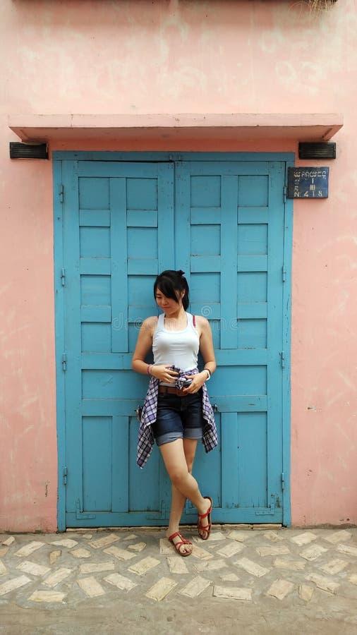Vêtements bleus avec la porte bleue et le fond rose photographie stock