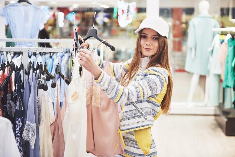 Vêtements d'achats de femme Client regardant l'habillement à l'intérieur dans le magasin Belle femelle caucasienne asiatique de s images stock