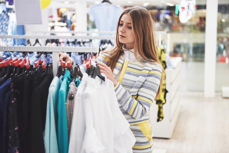 Vêtements d'achats de femme Client regardant l'habillement à l'intérieur dans le magasin Belle femelle caucasienne asiatique de s photos stock