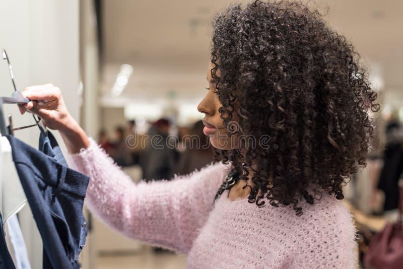 Vêtements d'achats de femme de couleur dans un magasin images libres de droits