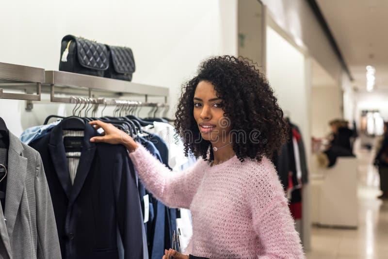 Vêtements d'achats de femme de couleur dans un magasin image stock