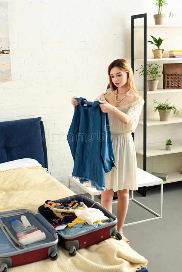 vêtements d'emballage de jeune femme dans la valise images libres de droits