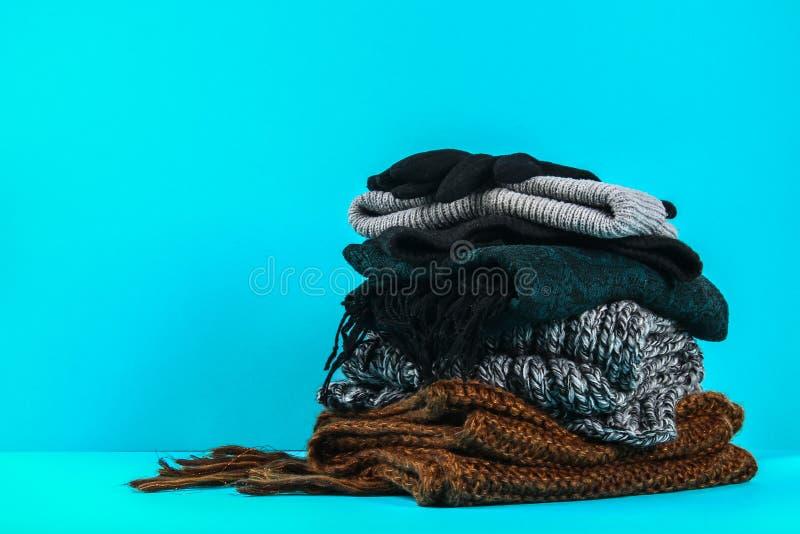 Vêtements d'hiver et d'automne, chapeaux, écharpes, gants sur un fond en pastel bleu image libre de droits