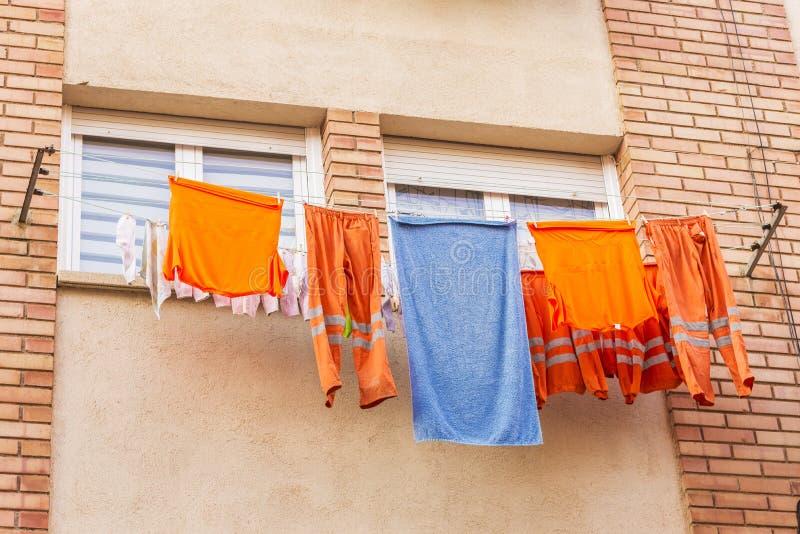 Vêtements d'un travailleur pendant d'une corde à linge pour sécher photos stock