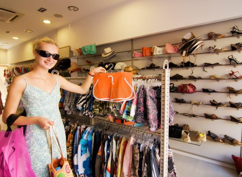 Vêtements de achat de fille blonde images stock