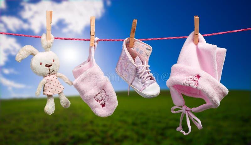 Vêtements de bébé sur la corde à linge dans extérieur photo stock