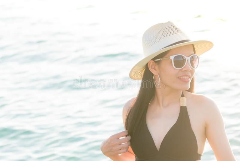 Vêtements de bain, chapeau de paille, et lunettes de soleil noirs sexy d'usage de femme détendant et apprécier des vacances à la  images stock