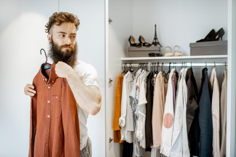 Vêtements de essai d'homme dans la garde-robe photographie stock libre de droits