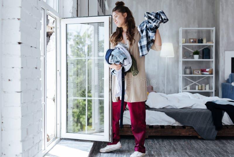 Vêtements de lancement de femme de son mari ex de la fenêtre images stock