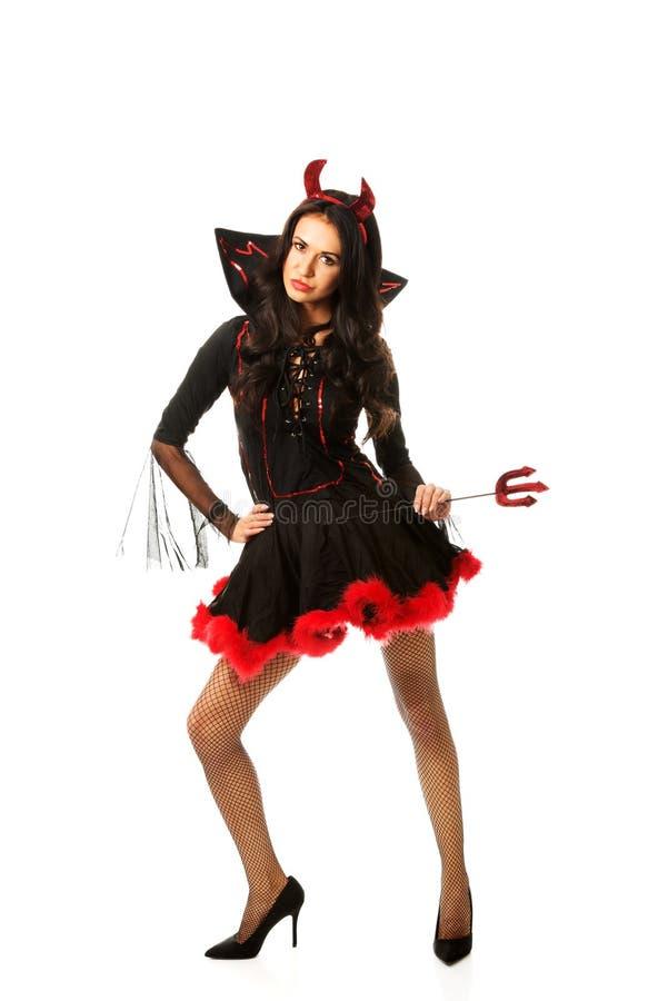 Vêtements de port de diable de femme tenant le trident image stock