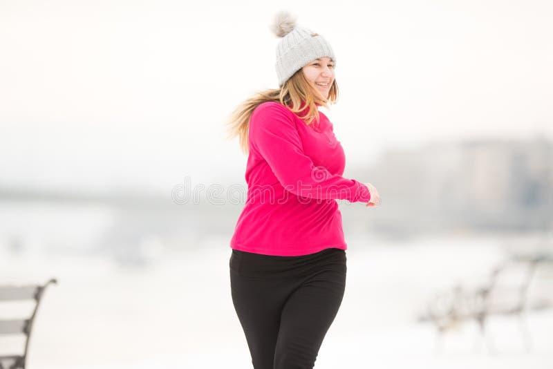 Vêtements de sport de port et fonctionnement de jolie fille sur la neige pendant le winte photos libres de droits