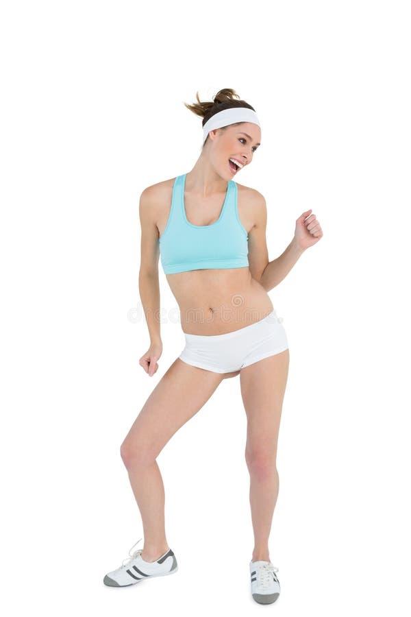 Vêtements de sport de port ponytailed heureux de danse de femme images stock