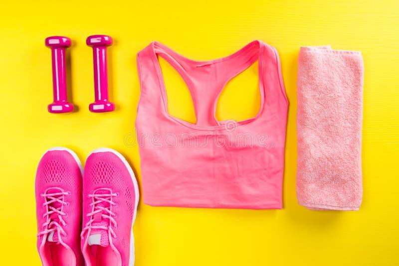 Vêtements de sport et accessoires roses pour la forme physique, sur un fond jaune photo libre de droits