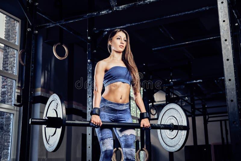 Vêtements de sport de port de femme de forme physique faisant le deadlift avec un barbell dans un gymnase photo libre de droits