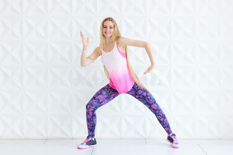 Vêtements de sport de port de femme heureuse faisant la pose de danse de forme physique près du mur blanc photographie stock
